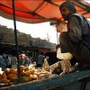 Kabul: A fruit vendor hunkers in the shade