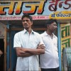 Patna: Two men stand vigilant outside their shop