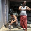 Patna: Two men work on the pavement outside their shop