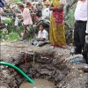 Patna: Residents cluster around the mud pit as a local NGO drills a new well in their slum