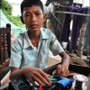 Battambang: A young boy mans the makeshift repair shop outside his home