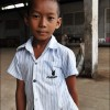 Battambang: A boy poses outside his home, an abandoned soft drink factory