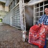 Sihanoukville: A woman and her dog relax outside their home, an abandoned train station