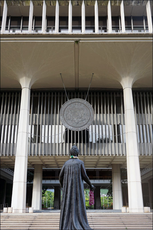 a statue of Queen Lili'uokalani stands in front of the Hawaii state capitol building