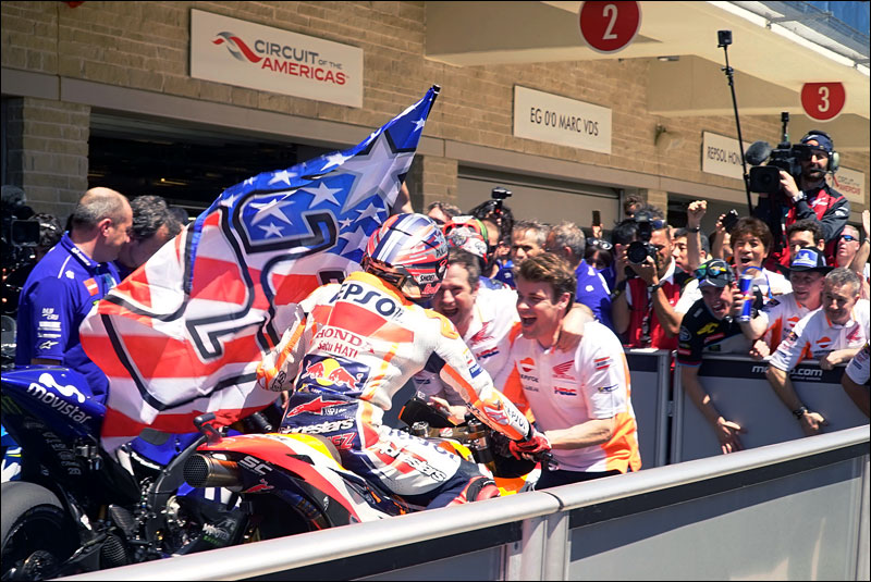 MotoGP race winner Marc Márquez arrives in parc fermé flying the flag of the late great Nicky Hayden at the 2018 Motorcycle Grand Prix of the Americas