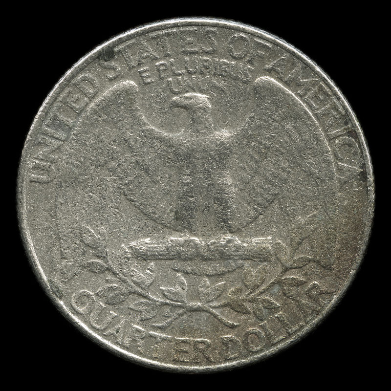 a weathered US 25 cent coin bearing the portrait of George Washington on one side and the bald eagle on the other