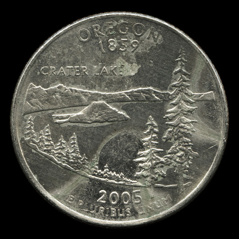 a weathered American 25 cent coin commemorating the state of Oregon bearing the portrait of George Washington on one side and Crater Lake on the other