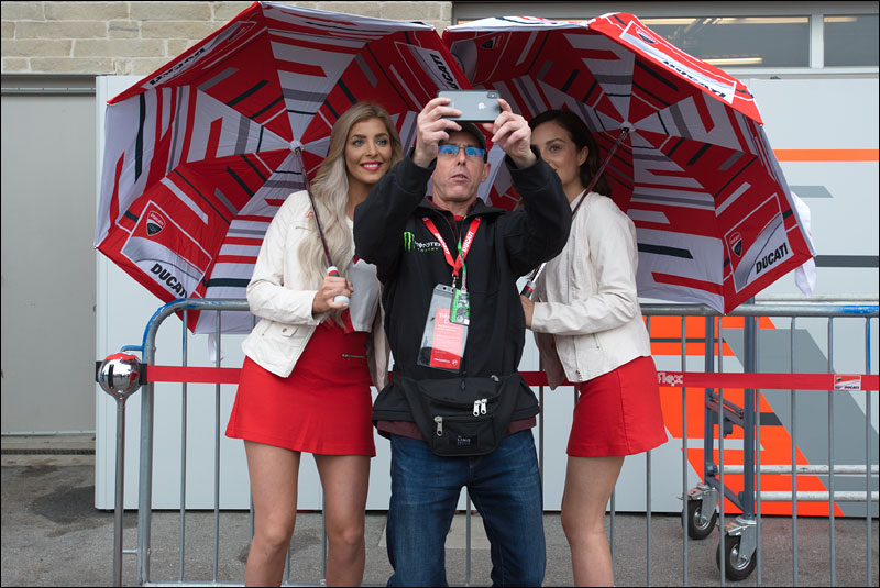 a fan takes a selfie with two Ducati Corse umbrella girls