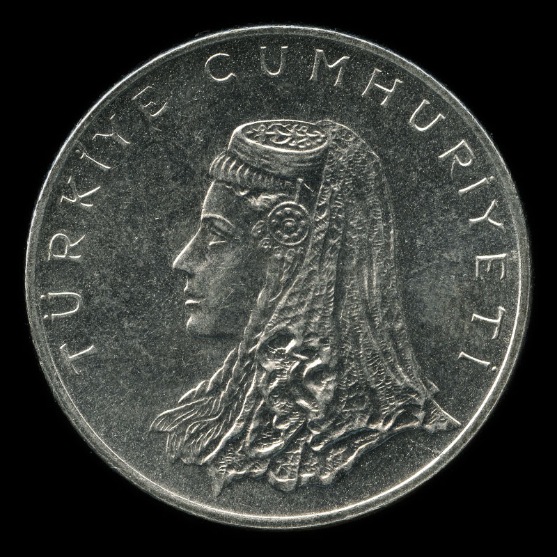 an obsolete 50 kuruş coin from Turkey showing a woman in Anatolian bridal dress on one side and a wheat stalk crossed with an olive branch on the other