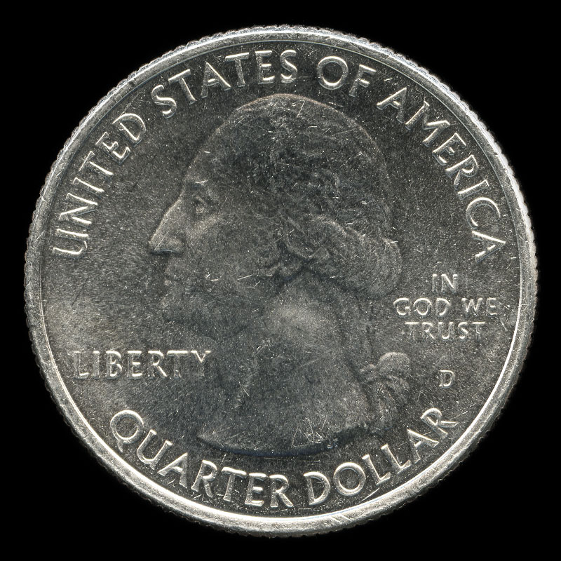 an American 25 cent coin featuring a portrait of George Washington on one side and a depiction of Mount Rushmore on the other